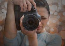 передний план фотографа принимая фото с отражением Запачканные коричневые света предпосылка и перекрытие Стоковое Изображение RF
