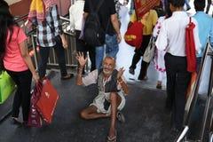 Передовица: Gurgaon, Дели, Индия: 6-ое июня 2015: Неопознанный старый бедный человек умоляя от людей на Gurgaon, Дели m Метро дор Стоковые Изображения