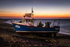 Перед рыболовной лодкой промышленного рыболовства захода солнца малой ждать быть запущенным от пляжа Hastings стоковое изображение