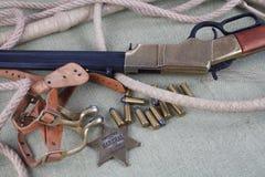 Период Диких Западов повторяя винтовку с значком боеприпасов и шерифа Стоковое Изображение