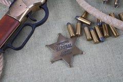 Период Диких Западов повторяя винтовку с значком боеприпасов и шерифа Стоковая Фотография