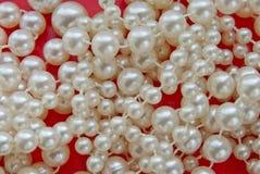 Перлы на красной предпосылке Стоковое Фото