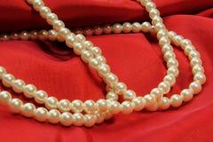Перлы на красной ткани Стоковое Фото