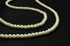 Перлы на черной ткани Стоковые Фотографии RF