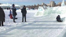 ПЕРМЬ, Россия, 06,2016 -го ФЕВРАЛЬ: Жизнерадостные дети идут для привода на скольжениях игры в маленьком городе льда акции видеоматериалы