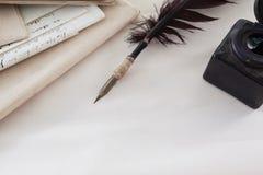 Перо Quill, бутылка чернил и правовые документы аранжировали на белой предпосылке Стоковое Фото