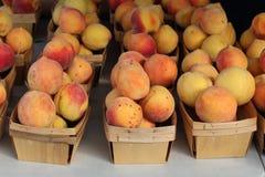 Персики в деревянных корзинах стоковые изображения