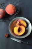 Персики в черной корзине провода, уменьшанном вдвое персике в шаре певтера Стоковые Изображения