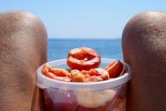 Персики на коленях Слезли персики в чашке на мужских волосатых ногах Каникулы пляжа морем Стоковое фото RF