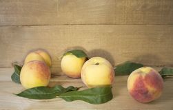 Персики на коричневой предпосылке Персики с зелеными листьями взгляд сверху в зеленых листьях Стоковая Фотография RF