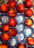 Персики на поднос в рынке Стоковая Фотография