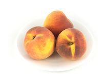 Персики на плите изолированной на конце белизны вверх Стоковые Изображения