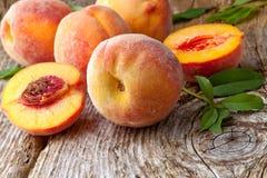 Персики с листьями на деревянной предпосылке Стоковая Фотография