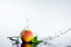 Персик в брызге воды Сочный персик с выплеском Стоковое Изображение