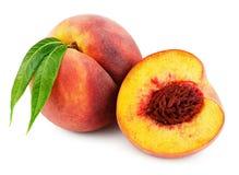 Персик с половиной и листья изолированные на белизне Стоковые Фото