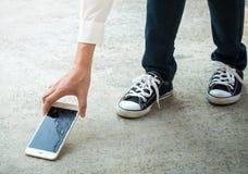 Персона выбирая сломанный умный телефон земли Стоковая Фотография