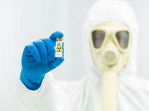 Персона в защитном костюме держа образец изотопа Стоковые Фото