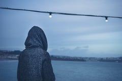 Персона в клобуке fairy светом на море Стоковое Изображение RF