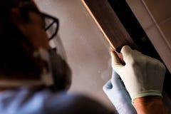 Персона в перчатках зашкурить рамку вокруг двери Стоковое фото RF