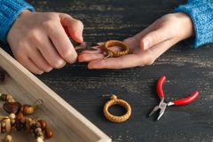 Персона делая ювелирные изделия используя провод, цепи и шарики и другие материалы с инструментами ремесла стоковые фотографии rf