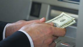Персона дела подсчитывая доллары приближает к ATM и деньги установки в бумажнике, креня акции видеоматериалы