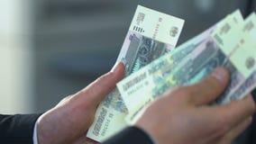 Персона дела подсчитывая русские рубли в банке, кладя деньги на депозит видеоматериал
