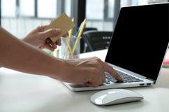 Персона держа кредитную карточку в руке и используя компьтер-книжку стоковые фотографии rf