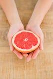 Персона держа кусок грейпфрута на таблице Стоковые Изображения RF