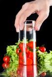 Персона держа стеклянной с водой и красными свежими томатами вишни, зеленым салатом позади изолированным на черноте Стоковое фото RF