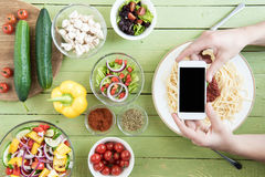 Персона держа smartphone с пустым экраном и фотографируя спагетти и свежие овощи на деревянном столе Стоковое Изображение RF
