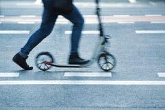 Персона ехать самокат в ходе улицы пешеходный переход Стоковая Фотография