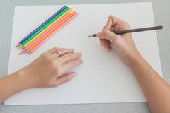 Персона делая эскиз к с покрашенными карандашами Стоковое Фото