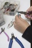 Персона делая ювелирные изделия с шариками и другими материалами с инструментами Стоковые Фото