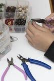 Персона делая ювелирные изделия с шариками и другими материалами с инструментами Стоковое Изображение