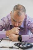 Персона дела думая крепко о налоге Принципиальная схема обложения Фото молодого подавленного бизнесмена сидя в офисе Стоковое фото RF
