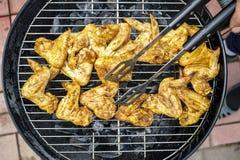Персона используя крыла цыпленка perevagachivaet пинцета кухни дальше Стоковое Изображение RF