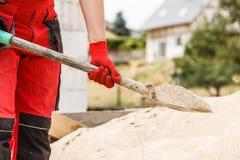 Персона используя лопаткоулавливатель на строительной площадке стоковое изображение rf