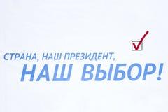 Персона кладет бюллетень в коробку во время избраний в России перед страной флага- наш президент наш выбор стоковые изображения rf