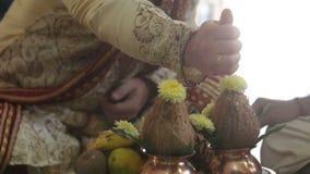 Персона крупного плана кладет семена в руку человека на индийской свадьбе