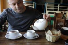 Персона лить зеленый чай стоковое фото