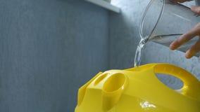 Персона льет воду в прибор уборщика пара перед использованием ее крупный план видеоматериал