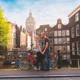 Персона 2 любовников в Амстердаме на предпосылке пестротканого дома в голландских руках стойки и владения стиля Стоковые Фотографии RF