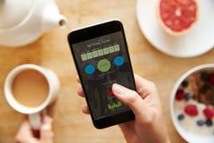 Персона на завтраке смотря фитнес App на мобильном телефоне Стоковое фото RF