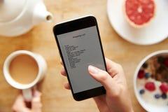 Персона на завтраке смотря, что сделать список на мобильном телефоне Стоковые Фото
