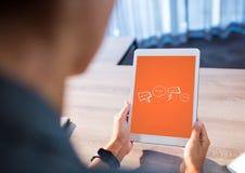 Персона на столе при таблетка показывая белые графики пузыря речи против оранжевой предпосылки Стоковое Изображение RF