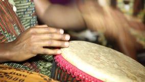 Персона не играя на барабанчике Jambe никакую сторону Крупный план рук человека барабаня вне ударом на африканской покрытой кож р акции видеоматериалы