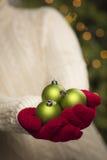 Персона нося сезонные красные Mittens держа зеленое рождество Ornam Стоковые Изображения RF