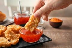 Персона окуная наггет цыпленка в chili Стоковые Изображения