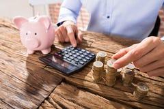 Персона подсчитывая монетки используя калькулятор Стоковая Фотография