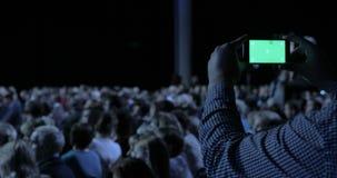 Персона принимая видео и фото на передвижном smartphone на конференцию Зеленый экран при включенный штейн luma Бизнес сток-видео